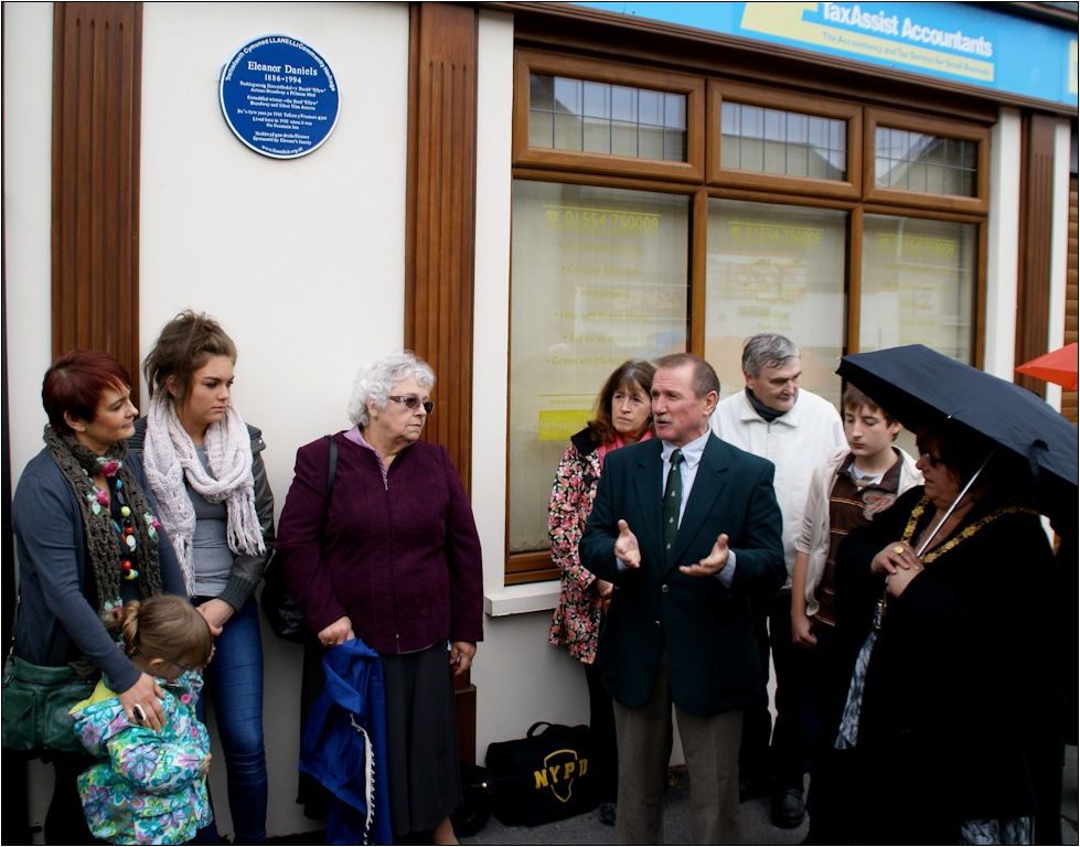 Llanelli Community Chairman John Hopkins addressing the gathering while Gwyneth Phillips (neice of Eleanor) stands by the plaque with her daughter and two granddaughters. To the right of the chairman is Cllr. Linda Steadman, Mayor of Llanelli Town Council.